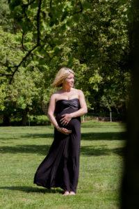 photo grossesse Elisa les cheveux dans le vent sur terrain arboré à Colleville