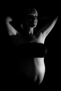 clair obscur et bras levés pour mettre en valeur son ventre de femme enceinte