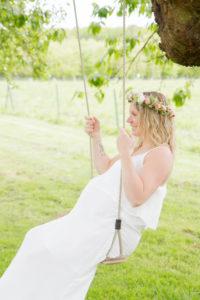 Leslie sur la balançoire avec une couronne de fleurs au style bohème chic