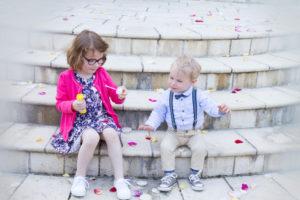 Ines & Augustin sur le perron de la mairie d eGouville sur mer entre bulles de savon et pétales de roses