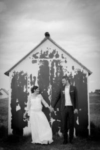 mariage bohème Le portrait des mariés face à une cabane sur la plage de Gouville sur mer