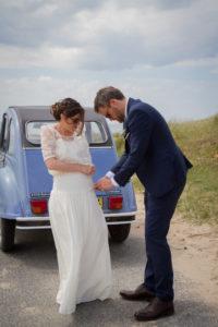 mariage bohème Nicolas aide Barbara à mettre sa robe de mariée sur la plage de Gouville sur mer