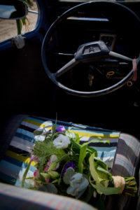 Le bouquet de la mariée posé sur le siège de la 2 CV