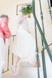 Contre jour de la robe et des chaussures de la mariée dans les escaliers de la mairie de Gouville sur mer