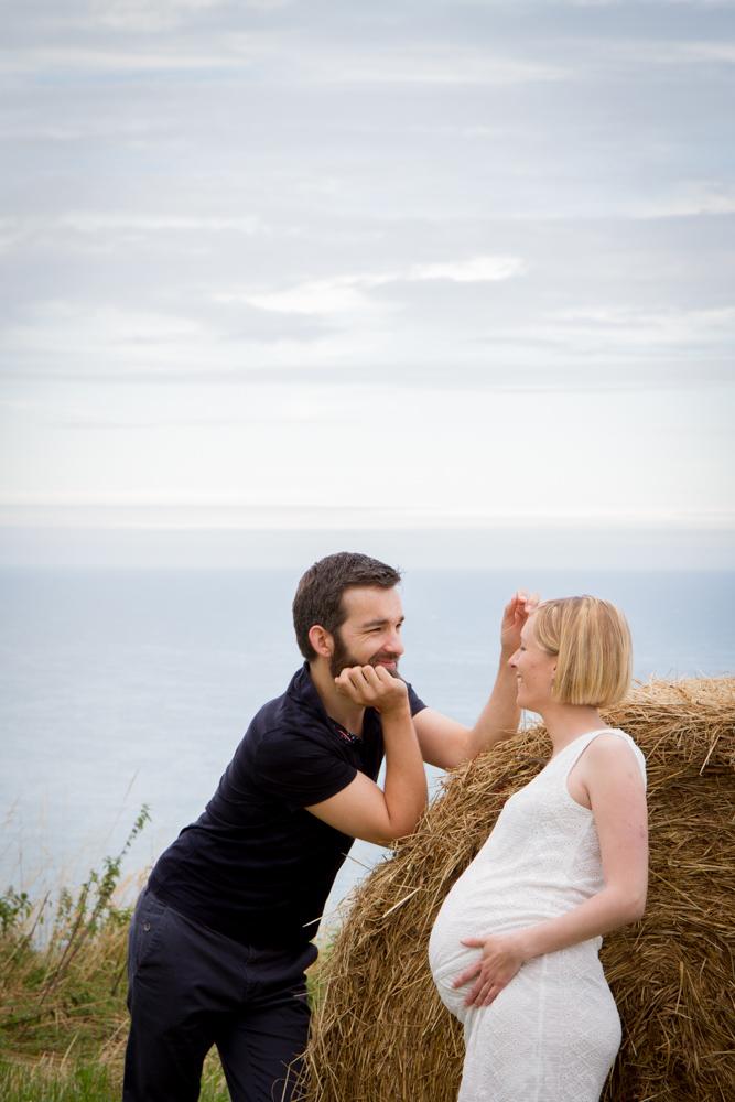 cedric et clara contre le ballot de paille pendant la séance grossesse à senneville-sur-fécamp en normandie