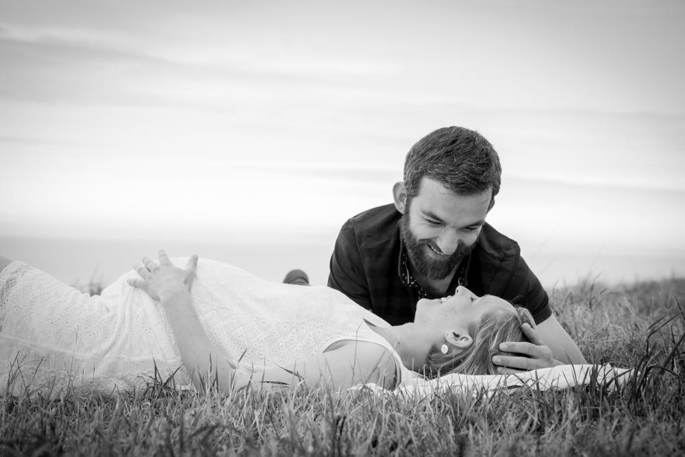 les amoureux allongés dans l'herbe se regardent pour la séance grossesse
