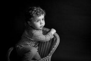 shooting du petit Lilio sur sa chaise en noir et blanc studio shooting en normandie