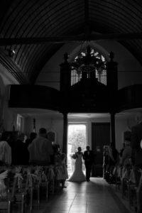 la mariée et son père s'avance devant l'hôtel église en normandie photo en noir et blanc