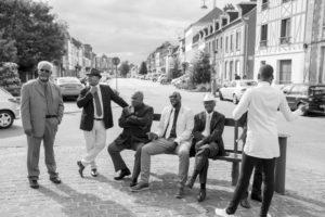 a la sortie de l'église au joli mariage d'élodie et clément les hommes patientent sur le banc en costume